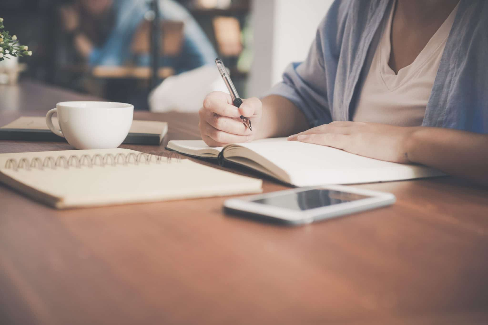 woman writing on a notebook beside teacup and tablet 733856 scaled